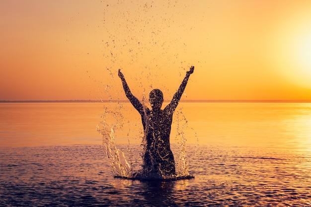 Man silhouet in kalm water bij zonsondergang