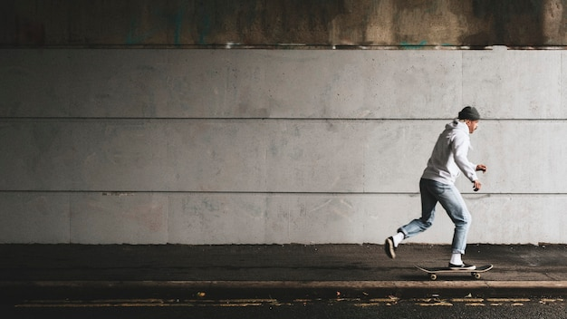 Man skateboarden onder een brug met ontwerpruimte van de stedelijke muur