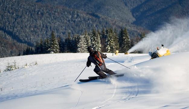 Man skiën op voorbereide helling met verse sneeuw