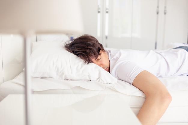 Man slapen op het bed in de slaapkamer
