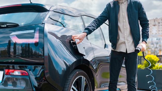 Man sluit auto's laadcontactdoos en houdt oplader bij laadstation