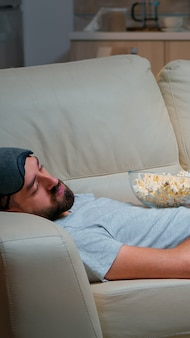 Man sluit zijn oog en valt in slaap op de bank in de woonkamer voor de tv, terwijl het televisie-entertainment aan is