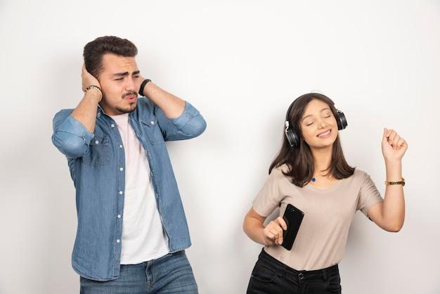 Man sluit zijn oren terwijl vrouw haar hart uit zingt.