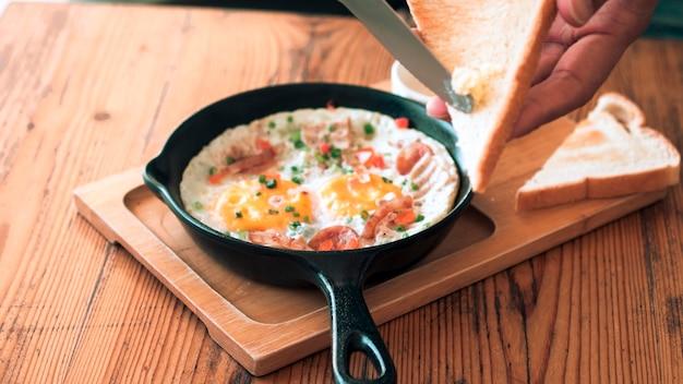 Man smeert boter op het brood met pan fried egg with toppings
