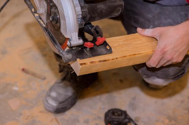Man snijden balk met behulp van een elektrische kettingzaag professionele gereedschappen