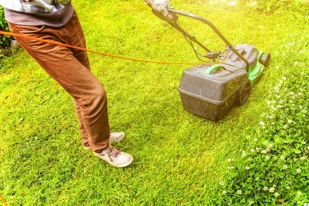 Man snijden groen gras met grasmaaier in de achtertuin. tuinieren land levensstijl achtergrond.