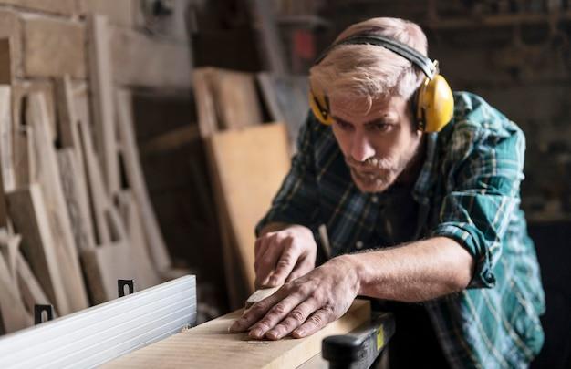 Man snijden houten planken
