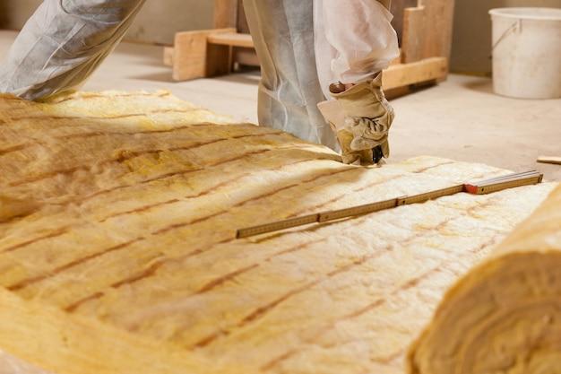 Man snijden isolatiemateriaal voor de bouw