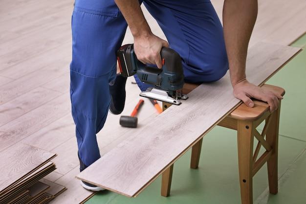 Man snijden laminaatplank met decoupeerzaag
