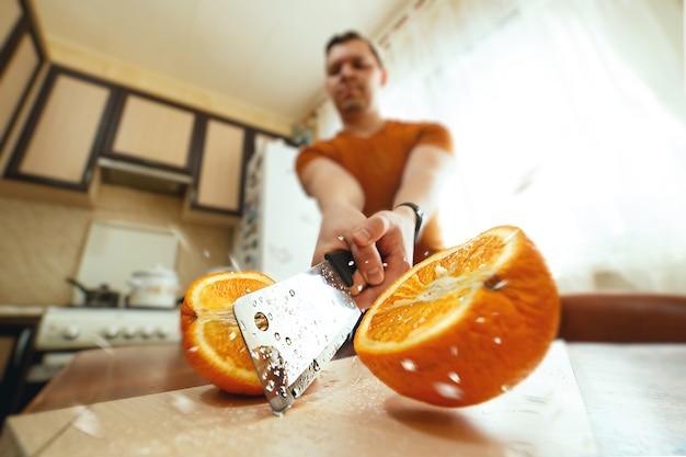 Man snijden van sappige sinaasappel doormidden met spatten in de keuken