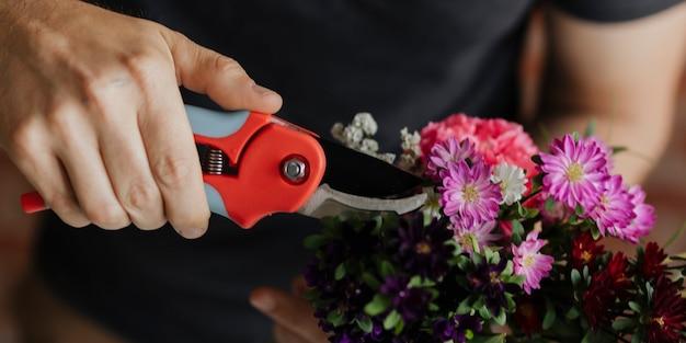 Man snijdt bloemen in zijn handen terwijl hij een boeket maakt