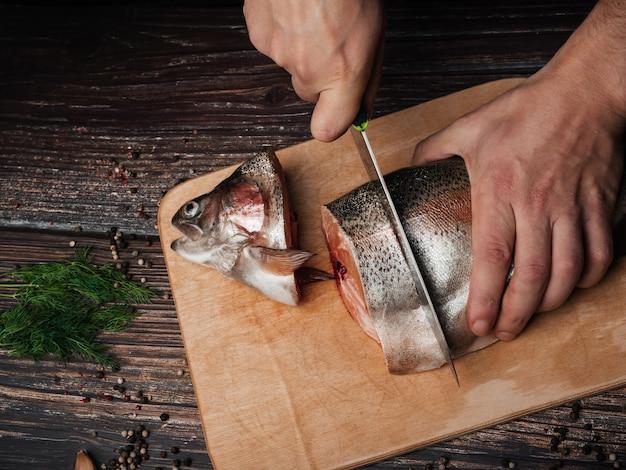 Man snijdt een forel met een mes op een bord