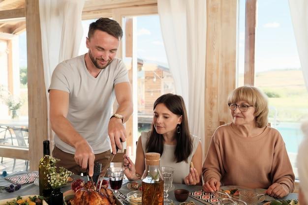 Man snijdt gebakken kalkoen terwijl hij aan tafel zit met zijn familie die ze thuis thanksgiving vieren