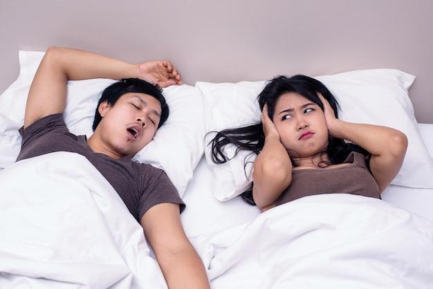 Man snurkt terwijl zijn vrouw oren bedekt met het kussen