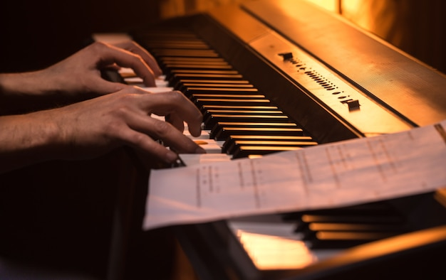 Man speelt de noten op de piano, close-up, mooie kleur achtergrond, het concept van muzikale activiteit