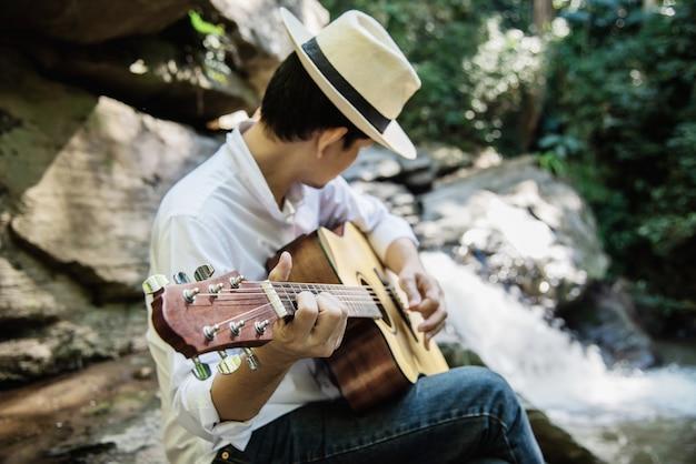 Man speelt gitaar dichtbij de waterval