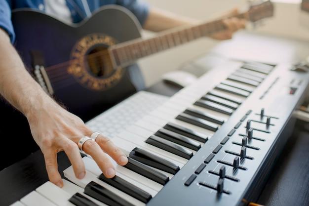 Man speelt gitaar en produceert elektronische soundtrack