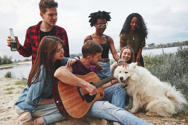 Man speelt gitaar. groep mensen hebben picknick op het strand. vrienden hebben plezier in het weekend.