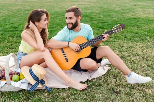 Man speelt gitaar voor zijn vriendin op de picknick in het park in de zomer op zonsondergang