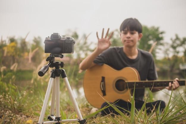 Man speelt gitaarles online, blogger video live streaming internet