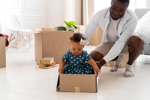 Man speelt met zijn kleine babymeisje terwijl hij beweegt