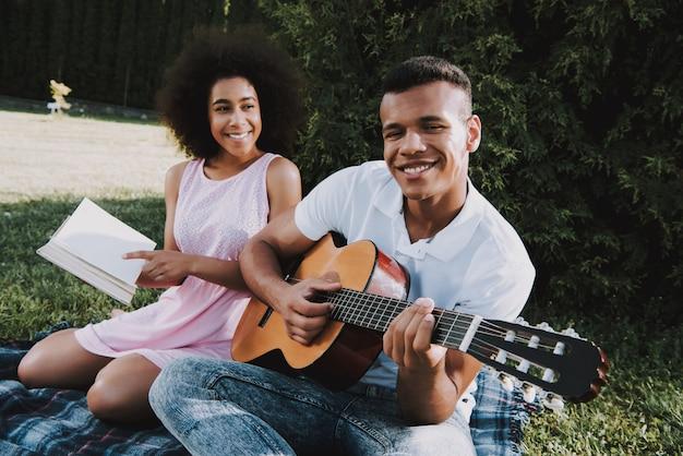 Man speelt op gitaar aan zijn meisje vrouw is boek aan het lezen
