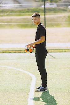 Man speelt socerl in het park. toernooi op mini-footbal. kerel in zwarte sportpakken.