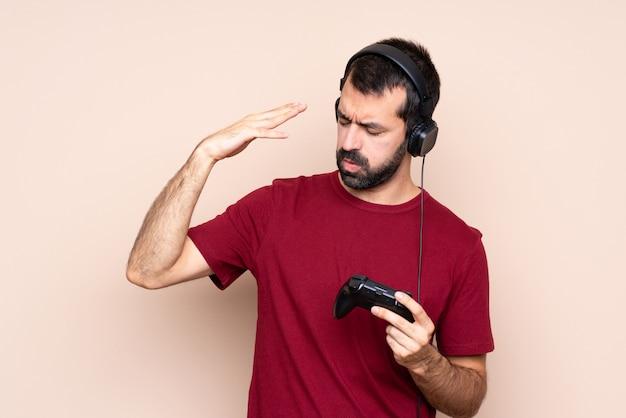 Man spelen met een video game controller met vermoeide en zieke uitdrukking