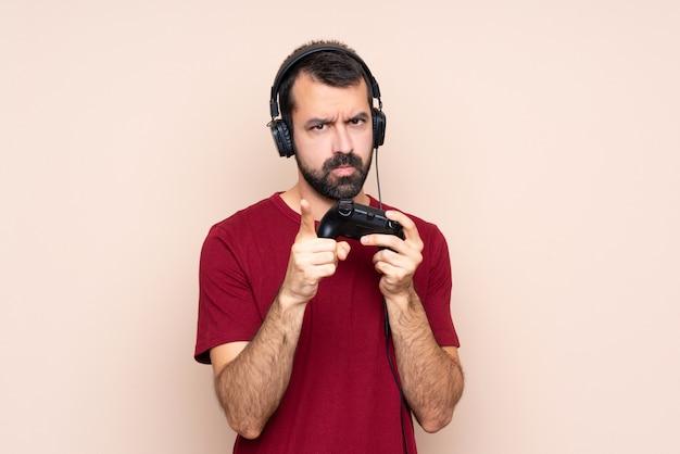 Man spelen met een video game controller over geïsoleerde muur gefrustreerd en wijzend op de voorkant