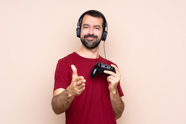 Man spelen met een video game controller over geïsoleerde muur handen schudden voor het sluiten van een goede deal