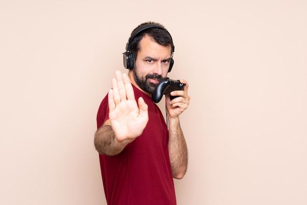 Man spelen met een video game controller over geïsoleerde muur maken stop gebaar en teleurgesteld