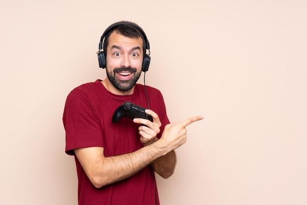 Man spelen met een video game controller over geïsoleerde muur verrast en wijzend kant