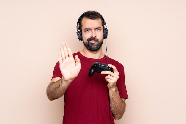 Man spelen met een video game controller stop gebaar maken