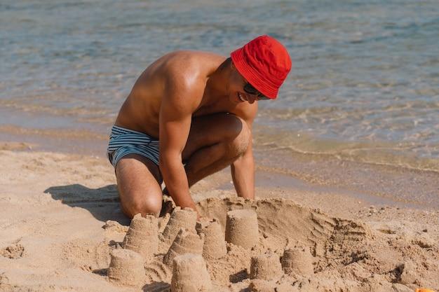 Man spelen met zand op het strand