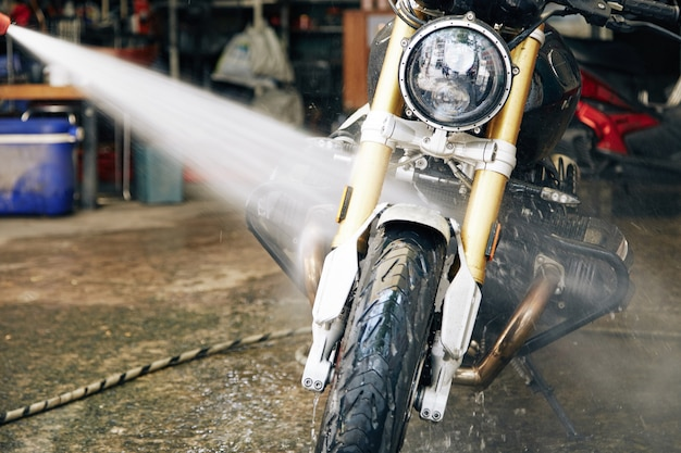 Man spoelt motorfiets met water in garage om vuil en vlekken te verwijderen