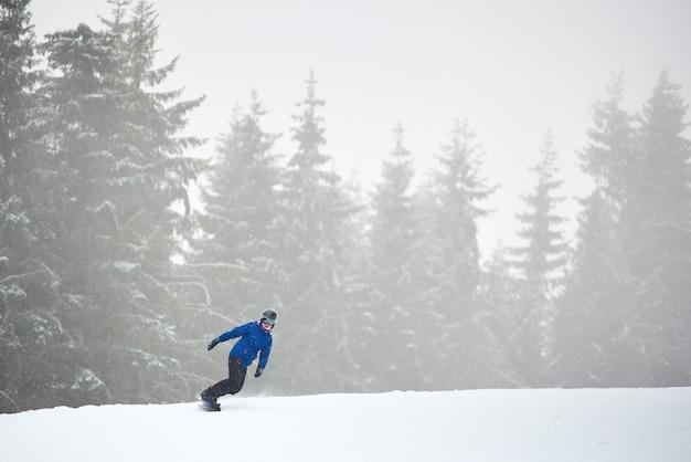 Man sportman snowboarden op vlakke besneeuwde weg in naaldbossen in zware sneeuwval