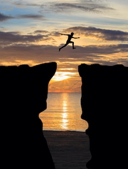 Man springen over klif op zonsondergang