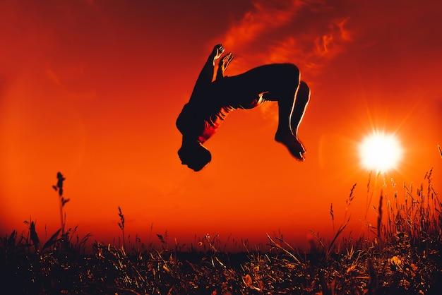 Man springt en doet een back-flip in de zomer in de natuur