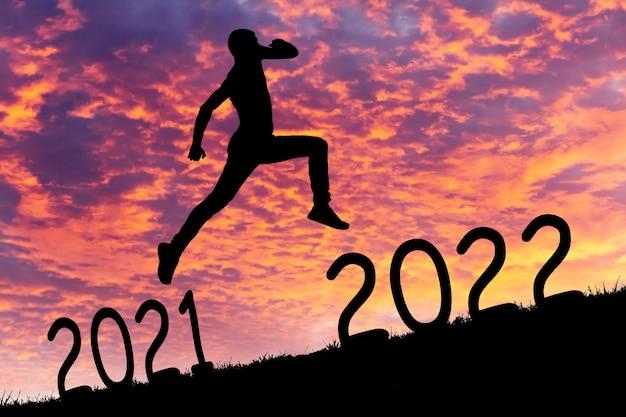 Man springt van 2021 tot 2022 jaar. silhouet rent of springt bergopwaarts van verleden naar toekomst. ambitie en uitdaging concept.