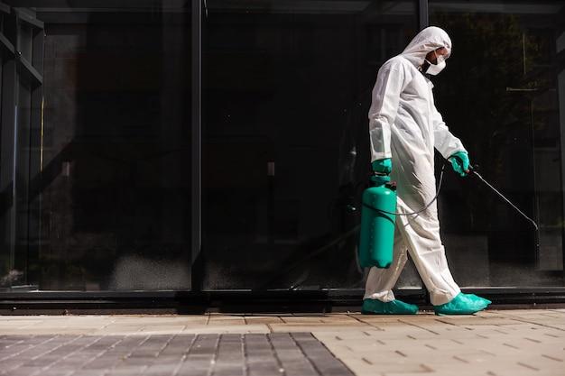 Man sproeien met desinfecterende straat tijdens coronavirus.