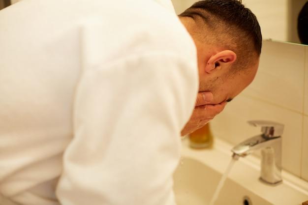 Man spuiten water op zijn gezicht na het scheren in de badkamer thuis