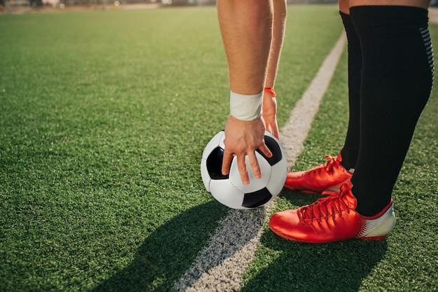 Man staan ar witte lijn geschilderd op gazon. hij houdt de bal er met handen op vast. guy draagt voetbalsneakers.