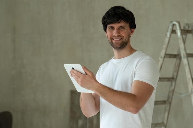 Man staan in nieuw appartement met behulp van tablet kiezen nieuw ontwerp van huis huis reparatie
