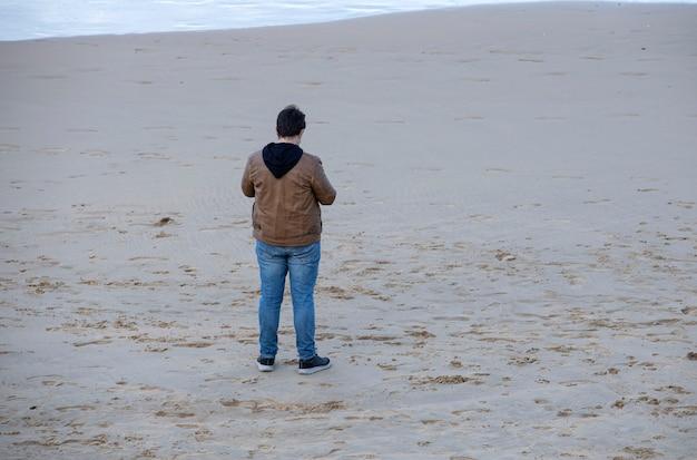 Man staan op het strandzand