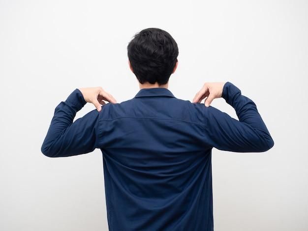 Man staande draai terug en raak zijn schouder witte achtergrond