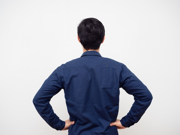 Man staande draai terug hand op zijn taille witte achtergrond
