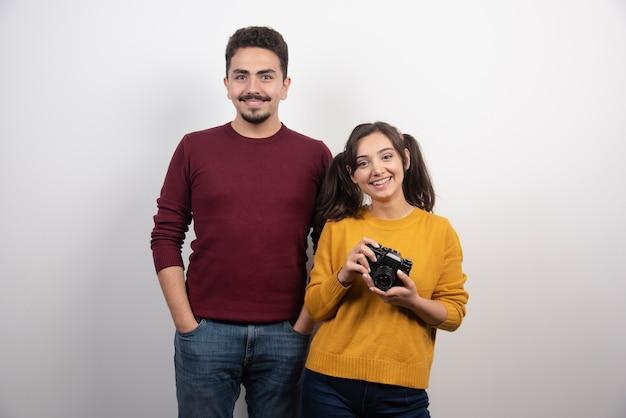 Man staande in de buurt van jonge vrouw met camera.