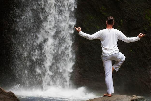 Man staande in meditatie yoga op rots bij waterval in tropisch bali