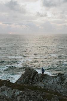 Man staande op de rotsen aan het strand bij zonsondergang