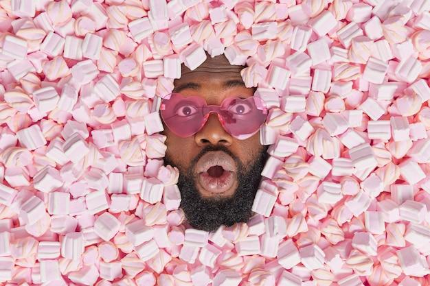 Man staart verrassend draagt trendy hartvormige zonnebril houdt mond open van verwondering omringd door marshmallows eet smakelijk smakelijk zoet dessert